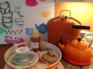My orange tea setup: tea cosy, kettle, tray with tea cup, honey, cookies.